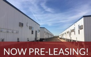 "A row of rectangular modular buildings, making up a workforce housing camp. Text superimposed on the image says ""Orla, Texas – Now Pre-Leasing!"""