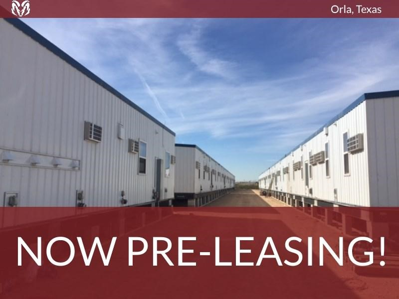 """A row of rectangular modular buildings, making up a workforce housing camp. Text superimposed on the image says """"Orla, Texas – Now Pre-Leasing!"""""""